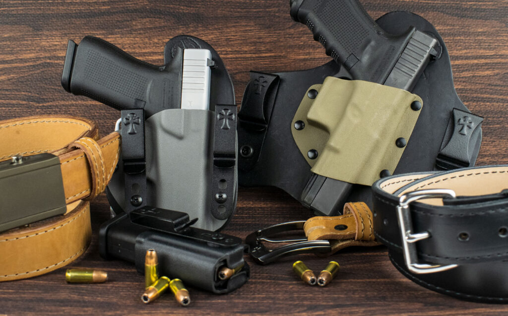 two pistol holsters with handguns, bullets and leather belts