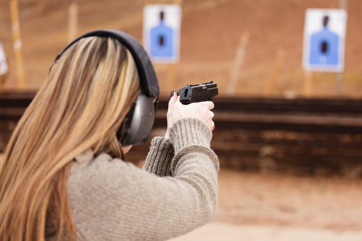 a woman wearing ear muffs and holding up a handgun to the target