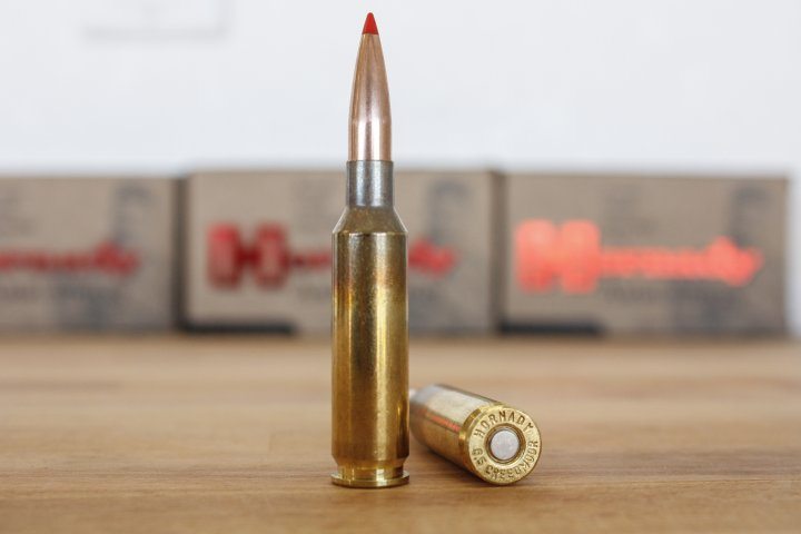two 6.5mm Creedmoor bullets standing and the other one is lying