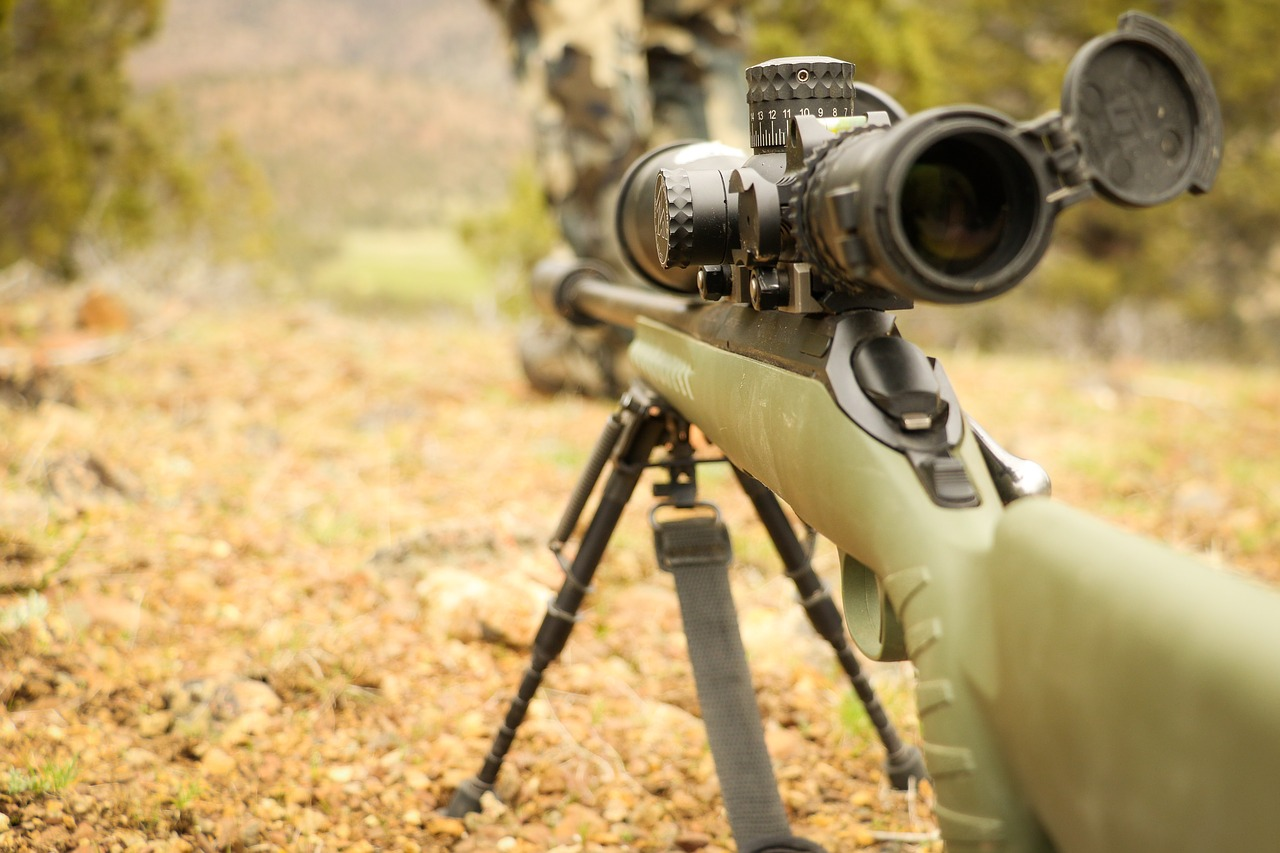 close-up photo behind a rifle with scope and bipod set up in the wild for hunting